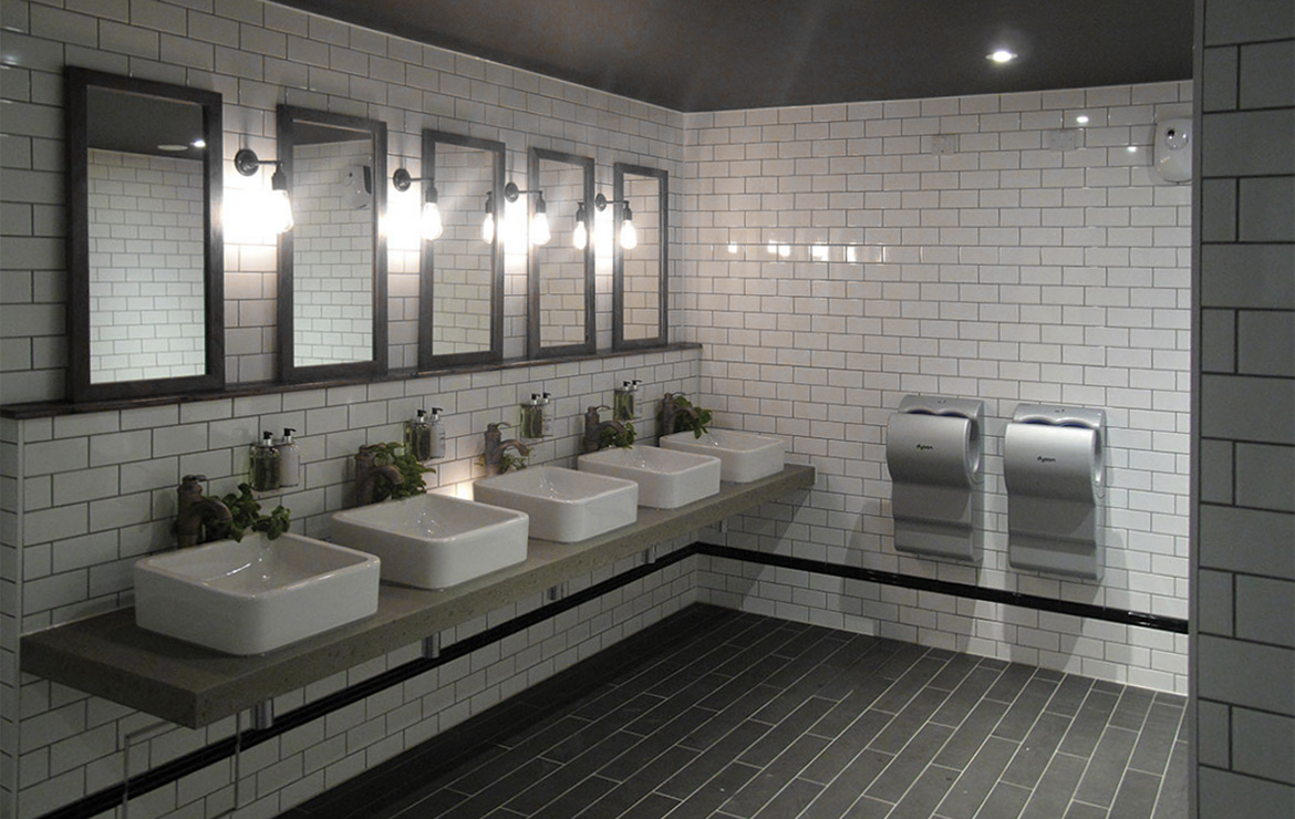 Blanco Brillo Liso 10x20 and London Negro Brillo 5x20. White tile Subway style commercial bathroom interior design.